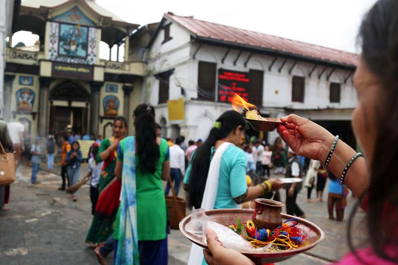 A devotee offers prayers to Lord Shiva in front of the Pashupatinath Temple in Kathmandu, on the  first Monday of the holy month of Shrawan, on July 18, 2016. Photo: RSS