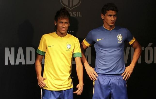 Brazilian soccer players Neymar (L) and Paulo Henrique Ganso pose with the national team's jersey in Rio de Janeiro February 3, 2012. REUTERS/Sergio Moraes/Files