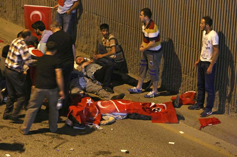 People react as bodies draped in Turkish flags are seen on the ground during an attempted coup in Ankara, Turkey on July 16, 2016. Photo: Reuters