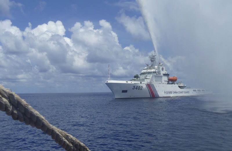 FILE - Chinese Coast Guard members approach Filipino fishermen as they confront each other off Scarborough Shoal in the South China Sea, also called the West Philippine Sea, on September 23, 2015. Photo: AP