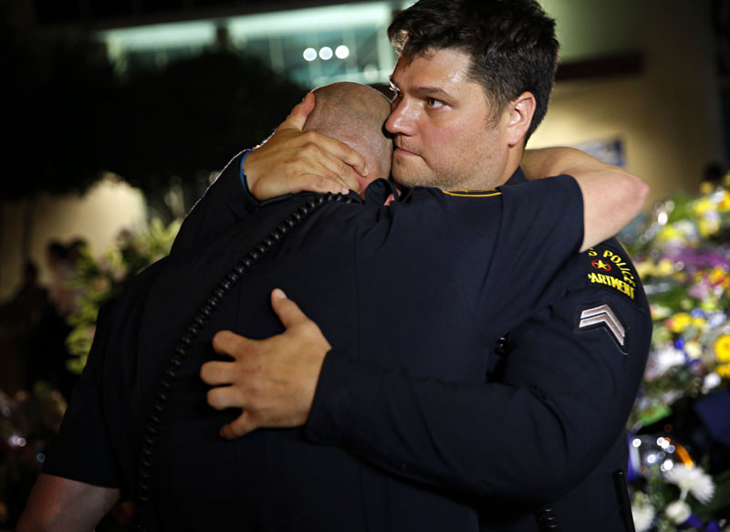 Dallas Police Department officers embrace as they visit a memorial in front of police headquarters, in Dallas, on Friday, July 8, 2016. Photo: G.J. McCarthy/The Dallas Morning News via AP