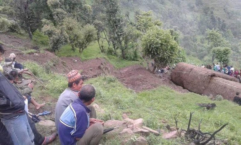 Locals look at Durga Bahadur Malla's house that was hit by a landslide, killing five members of Malla's family. Photo: THT