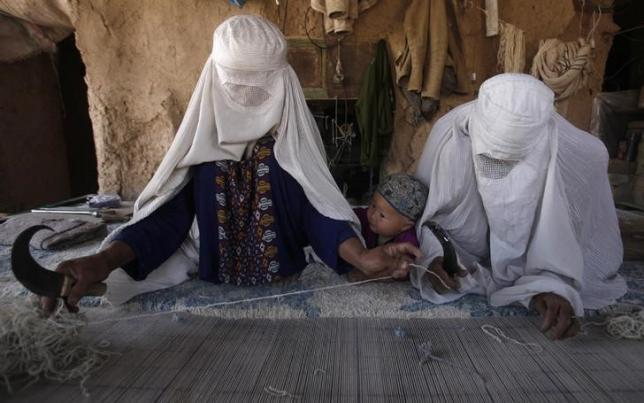Ethnic Hazara Afghan women weave a carpet at a makeshift workshop at their house in Khorasan Refugee Camp, on the outskirts of Peshawar April 17, 2014. REUTERS/Fayaz Aziz/Files