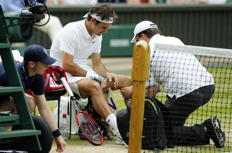 FILE - Roger Federer of Switzerland receives medical attention during his men's semifinal singles match against Milos Raonic of Canada at the Wimbledon Tennis Championships in London, on July 8, 2016. Photo: AP
