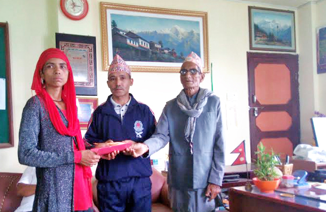 Local Development Officer Bharat Kumar Sharma (centre) handing over land ownership certificate to Pabitra Damai at the DDC Office, in Rukum, on Monday, July 11, 2016. Photo: THT