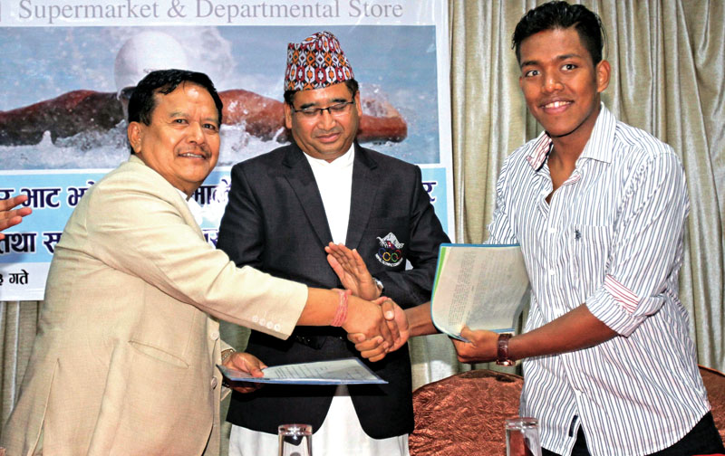 Managing Director of Bhatbhateni Supermarket Min Bahadur Gurung (left) and swimmer Shirish Gurung exchange MoU as NOC President Jeevan Ram Shrestha looks on during the signing ceremony in Kathmandu on Thursday.