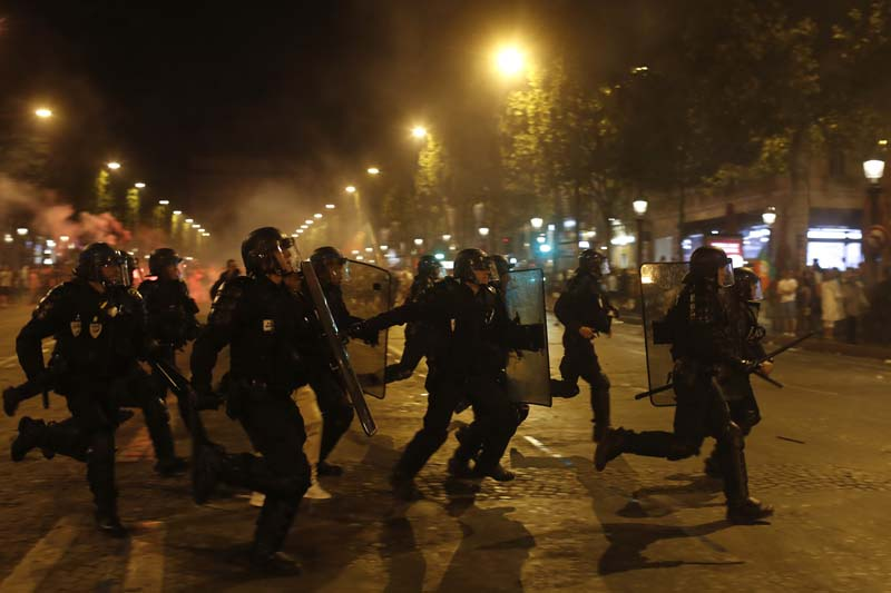 Riot police officers take position during scuffles on the Champs Elysees avenue after the Euro 2016 final soccer match between Portugal and France, early Monday, July 11, 2016 in Paris. Photo: AP