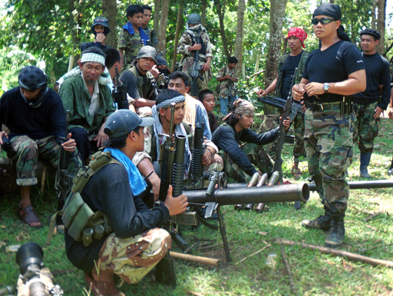 FILE - Abu Sayyaf spokesman Abu Sabaya (right foreground) stands with militants in Basilan, the Philippines. Abu Sayyaf, a group in the southern Philippines that professes radical Islamic ideology but which is better known for banditry and kidnappings, has declared allegiance to the Islamic State. Photo: AP