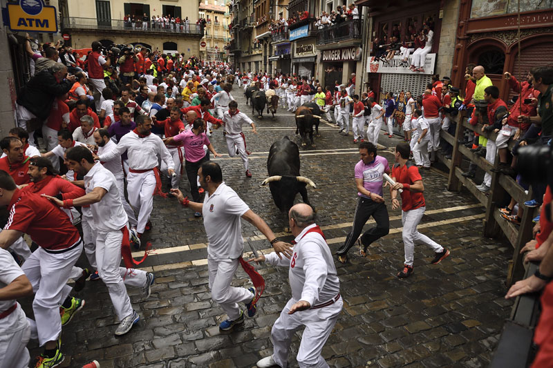 Revelers run around Nunez del Cubillo's fighting bulls on the Estafeta corner during the seventh day of the running of the bulls at the San Fermin Festival, in Pamplona, northern Spain, on Wednesday, July 13, 2016. Photo: AP