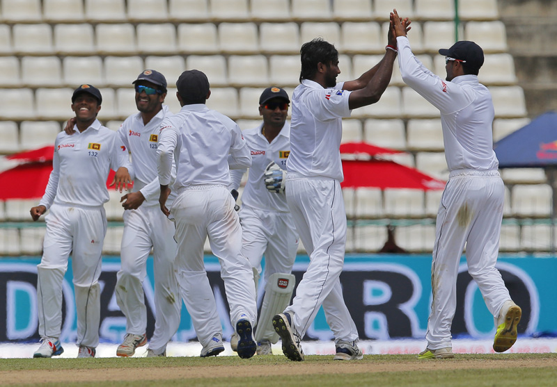 Sri Lankan team members congratulate their bowler Nuwan Pradeep Perera, second left, for the dismissal of Australia's Peter Nevill during day two of the first test cricket match between Sri Lanka and Australia in Pallekele, Sri Lanka, Wednesday, July 27, 2016. Photo: AP