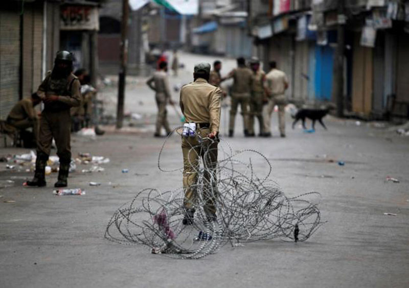 An Indian policeman pulls concertina wire to lay a barricade on a road during a curfew in Srinagar July 12, 2016. Photo: Reuters