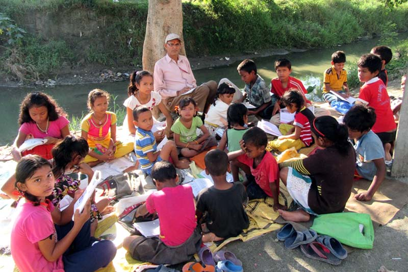 Children of marginalised and Dalit community read under the shelter of a tree near the Tengra stream in Itahari district, on Saturday, July 30, 2016. Teacher, Chandra Gautam, has been running free tuition classes for the students since two decades. Photo: RSS