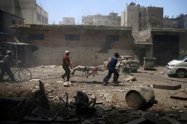 Men transport a casualty at a site hit by airstrikes in the rebel held Douma neighbourhood of Damascus, Syria, July 25, 2016. REUTERS/Bassam Khabieh