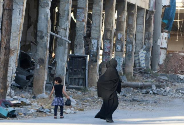 Residents walk past damaged buildings in the rebel held area of Aleppo's Bab al-Hadeed district, Syria, June 27, 2016. REUTERS/Abdalrhman Ismail