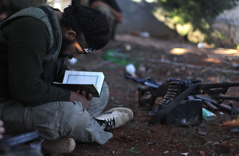 FLE -  A Syrian rebel reads Quran during clashes with government forces in Aleppo, Syria, on  November15, 2012. Photo: AP