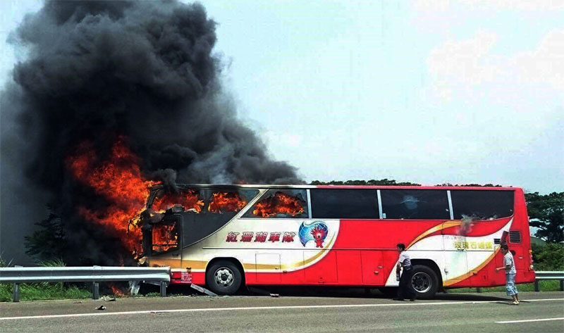 A policeman and another man try to break the windows of a burning tour bus on the side of a highway in Taoyuan, Taiwan, on Tuesday, July 19, 2016. Photo: Yan Cheng/Scoop Commune via AP