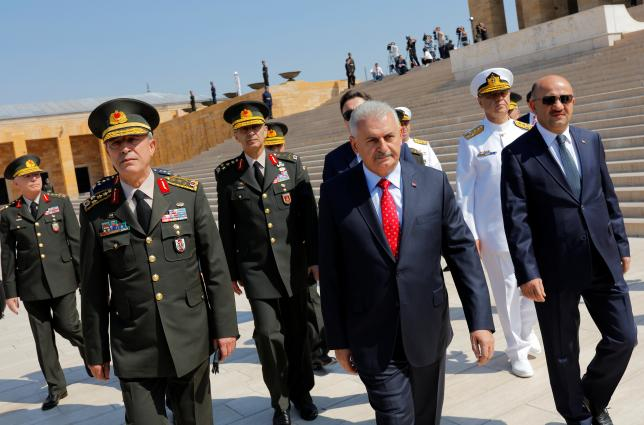 Turkey's Prime Minister Binali Yildirim (C), flanked by Chief of Staff General Hulusi Akar (L), Defense Minister Fikri Isik (R) and the country's top generals, leaves Anitkabir, the mausoleum of modern Turkey's founder Mustafa Kemal Ataturk, after a wreath-laying ceremony ahead of a High Military Council meeting in Ankara, Turkey, July 28, 2016. REUTERS/Umit Bektas