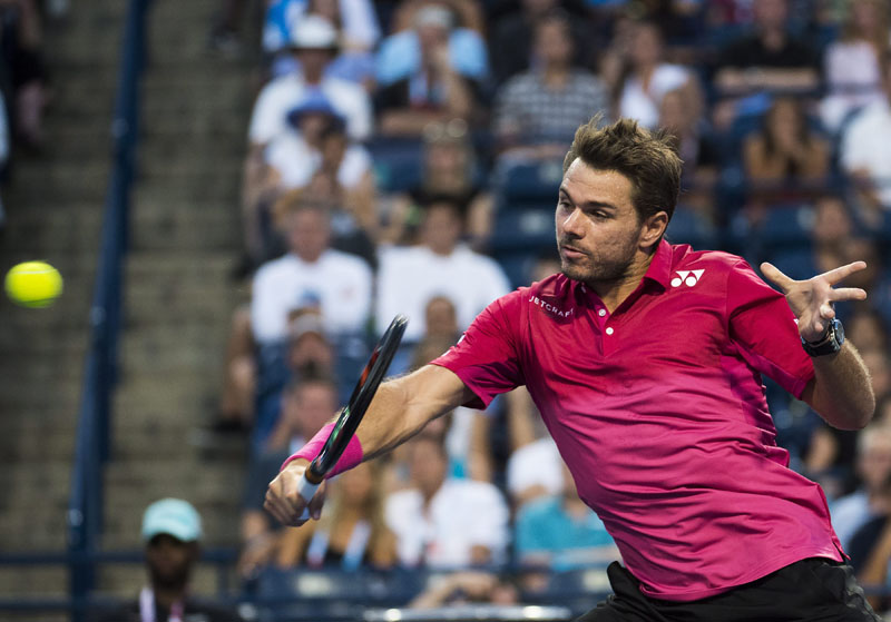 Stan Wawrinka of Switzerland returns the ball to Mikhail Youzhny of Russia at the Rogers Cup tennis tournament in  in Toronto, on Tuesday, July 26, 2016. Photo: Nathan Denette/The Canadian Press via AP