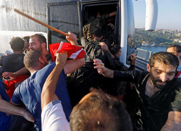 Soldiers push each other to board a bus to escape the mob after troops involved in the coup attempt surrendered on the Bosphorus Bridge in Istanbul, Turkey July 16, 2016. REUTERS/Murad Sezer/File Photo