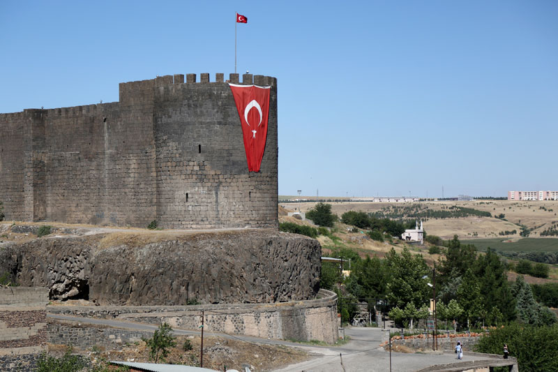 A Turkish flag hangs on the historical city walls at one of the entrance of Sur district in Diyarbakir, Turkey July 11, 2016. Photo: Reuters/File