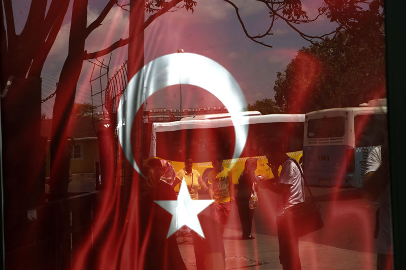People reflected on glass with Turkish a flag at a bus station in Istanbul, on Monday, July 25, 2016. Photo: AP