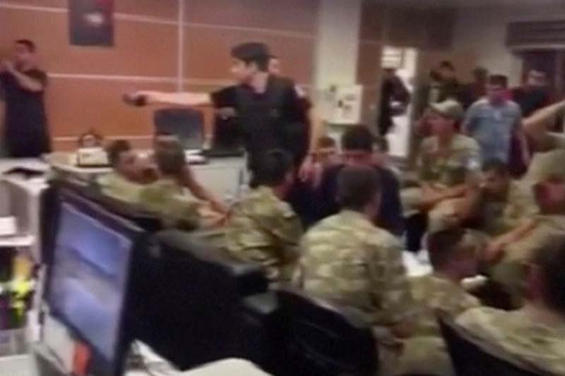 Still frame taken from amateur video obtained by Reuters on July 16, 2016 shows soldiers seated in a room with policemen standing, in Ankara, Turkey. Photo: Amateur Video via Reuters TV