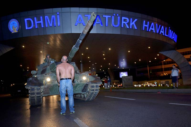 A man stands in front of a Turkish army tank at Ataturk airport in Istanbul, Turkey on July 16, 2016. Photo: IHLAS via Reuters