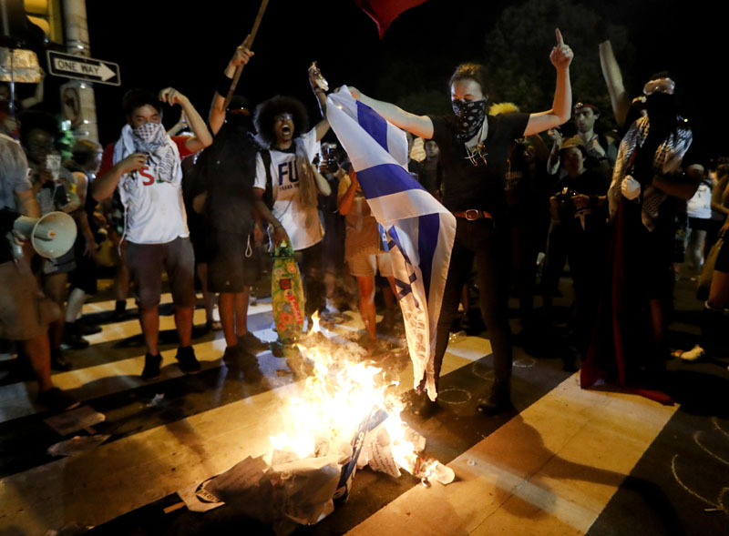 Demonstrators burn a flag during a protest in Philadelphia, on Tuesday, July 26, 2016, during the second day of the Democratic National Convention. Photo: AP
