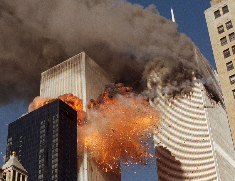 Smoke billows from World Trade Center Tower 1 and flames explode from Tower 2 as it is struck by American Airlines Flight 175, in New York on September 11, 2001. Photo: AP/File