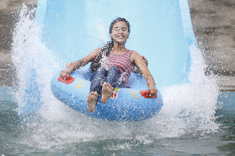 A woman slides into a swimming pool at the Whoopee Land Amusement and Water Park in Chobhar, Kirtipur on Saturday, July 9, 2016. Photo: Skanda Gautam