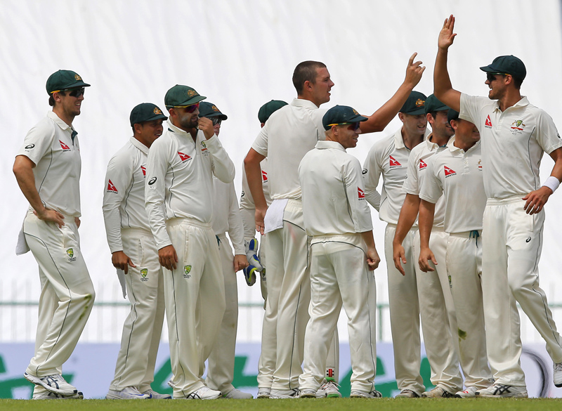 Australian teammates congratulate their bowler Josh Hazlewood, center, for taking the wicket of Sri Lanka's Kusal Mendis, unseen, on day one of the first test cricket match between Sri Lanka and Australia in Pallekele, Sri Lanka, Tuesday, July 26, 2016. Photo: AP