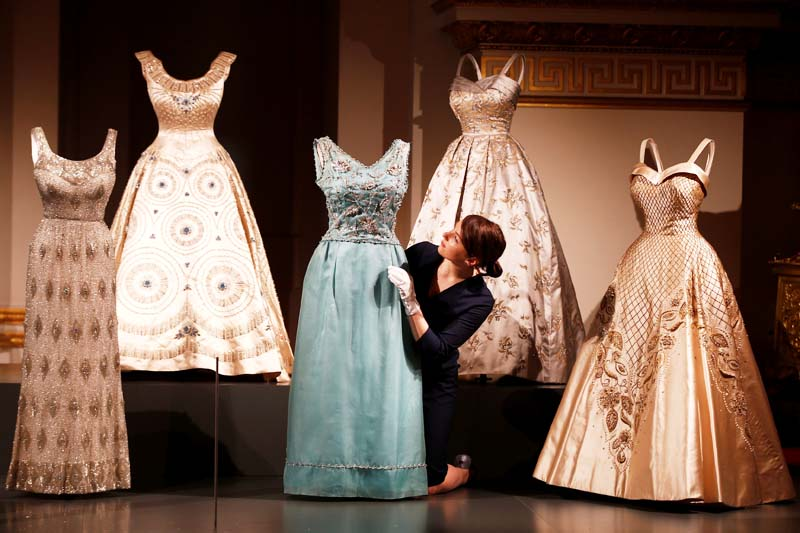 A member of the Royal Collection Trust, poses for photographers next to Britain's Queen Elizabeth's evening gowns, ahead of the opening of an exhibition entitled 'Fashioning a Reign: 90 Years of Style from the Queen's Wardrobe', at Buckingham Palace, in London, Britain on July 21, 2016. Photo: Reuters