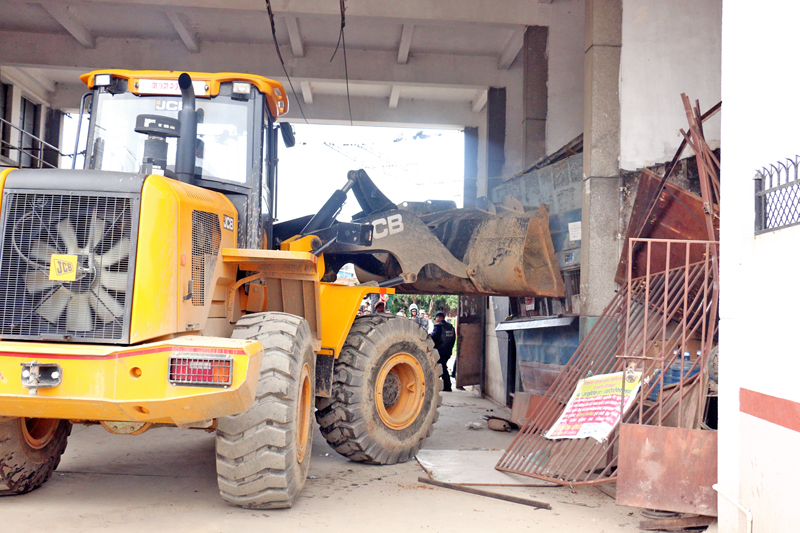 A bulldozer dismantles illegally built makeshift structures in the premises of Department of Transport Management Office, in Minbhawan, Kathmandu, on Sunday, July 31, 2016. Photo: RSS