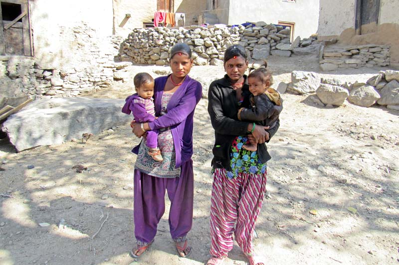 Two teenage girls in Sappata VDC of Bajura district pose for a photograph with their children. Child marriage is still prevalent in the district. Photo: Prakash Singh/File