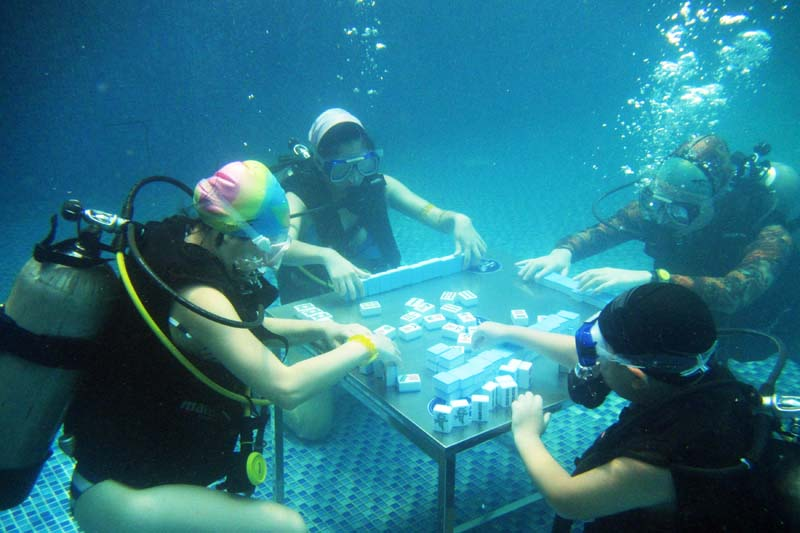 Divers play mahjong in a swimming pool during a hot summer day in Chongqing, China on July 17, 2016. Photo: Reuters
