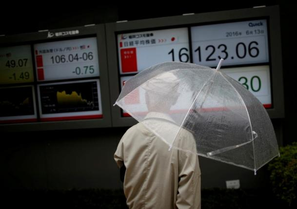 A man looks at an electronic board showing the recent exchange rate between Japanese yen against the U.S. dollar and Japan's Nikkei average (R) outside a brokerage in Tokyo, Japan, June 13, 2016. REUTERS/Issei Kato/File Photo