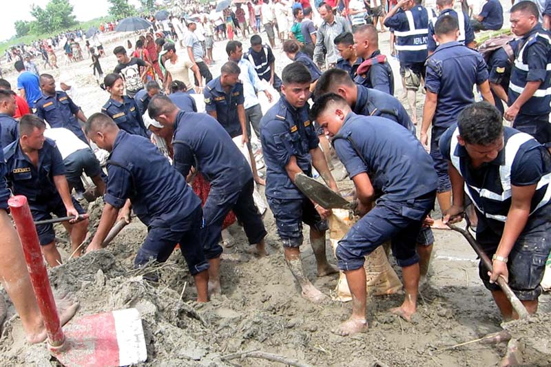 Police personnel, with locals, build an embankment to change the course of water that entered a human settlement back to the Batraha stream, in Hasandaha of Morang district, on Sunday, July 31, 2016. Photo: RSS
