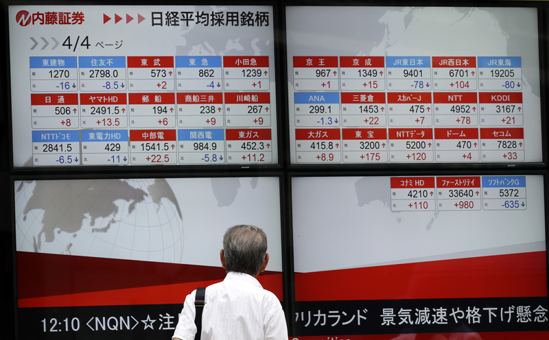 A man looks at an electronic stock board showing Japan's Nikkei 225 index at a securities firm in Tokyo, Tuesday, July 19, 2016. Photo: AP