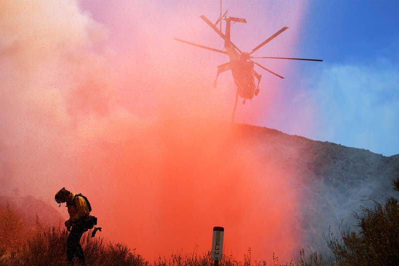 A fire fighter is sprayed with retardant as a helicopter makes a drop as emergency workers continue to battle the so-called Sand Fire in the Angeles National Forest near Los Angeles, California, United States on July 25, 2016. Photo: Reuters
