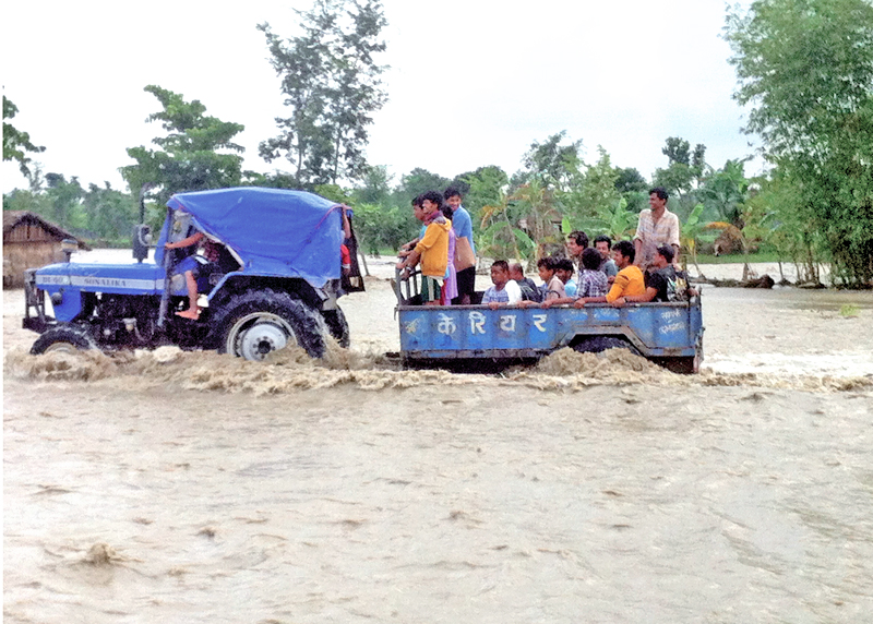 Locals being taken to safer places in a tractor after the flooded Bakraha River inundated wards no 4 and 5, in Urlabari, Morang, on Sunday, July 24, 2016. Photo: THT