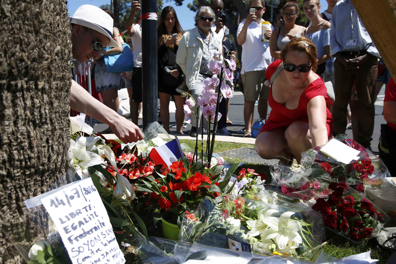 A woman places a bouquet of flowers as people pay tribute near the scene where a truck ran into a crowd at high speed killing scores and injuring more who were celebrating the Bastille Day national holiday, in Nice, France, July 15, 2016. Photo: Reuters