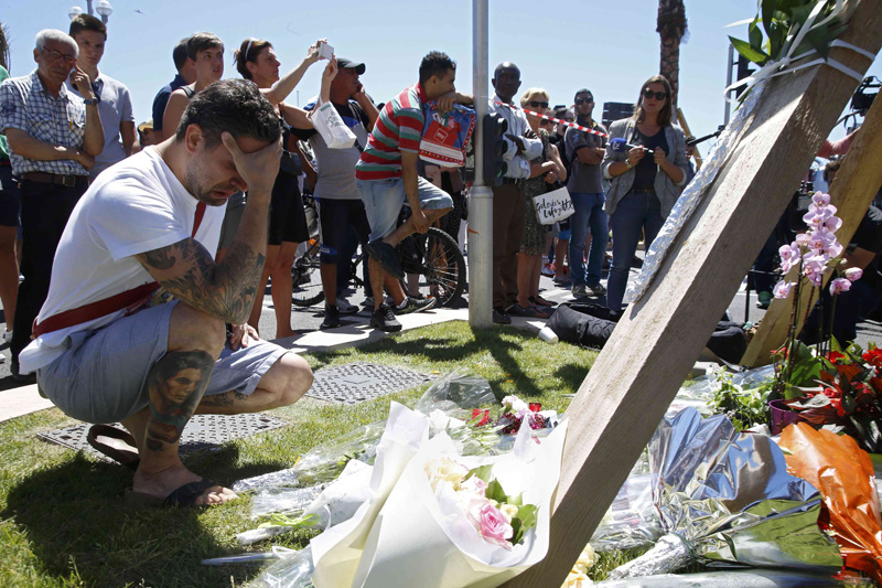 A man reacts near bouquets of flowers near the scene where a truck ran into a crowd at high speed killing scores and injuring more who were celebrating the Bastille Day national holiday, in Nice, France, July 15, 2016. Photo: Reuters