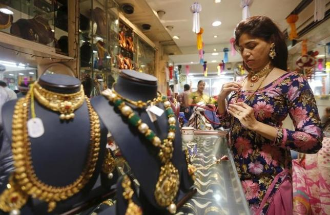 A customer tries a gold necklace at a jewellery showroom on the occasion of Dhanteras, a Hindu festival associated with Lakshmi, the goddess of wealth, at a market in Mumbai, India, November 9, 2015.  REUTERS/Shailesh Andrade