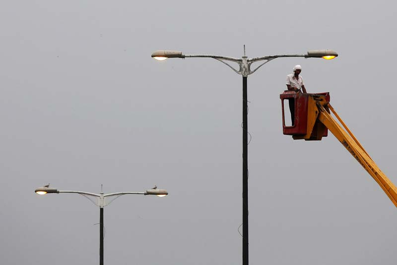 A man repairs a streetlight on a rainy day in New Delhi, India on July 26, 2016. Photo: Reuters