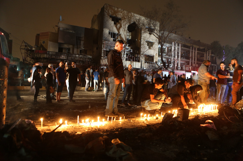 People light candles at the scene of a massive car bomb attack in Karada, a busy shopping district where people were shopping for the upcoming Eid al-Fitr holiday, in the center of Baghdad, Iraq, Sunday, July 3, 2016.Photo: AP