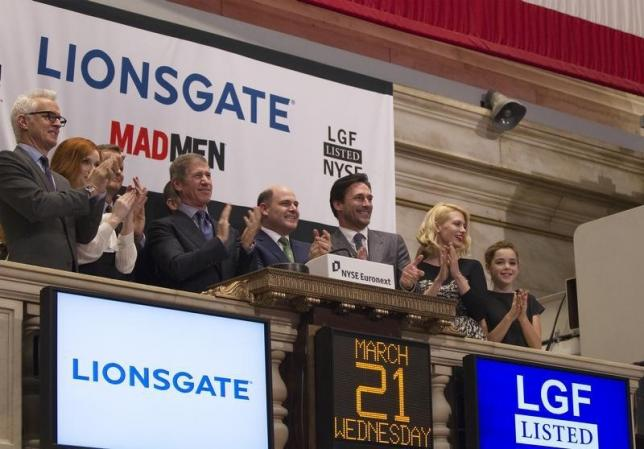 CEO of Lions Gate Entertainment, Jon Feltheimer (3rd L), claps with actors from the show Mad Men (L-R) John Slattery, Christina Hendricks, Jon Hamm, January Jones, and Kiernan Shipka with the show's creator Matthew Weiner (C) while visiting the New York Stock Exchange to ring the opening bell in New York, March 21, 2012.   Photo: Reuters