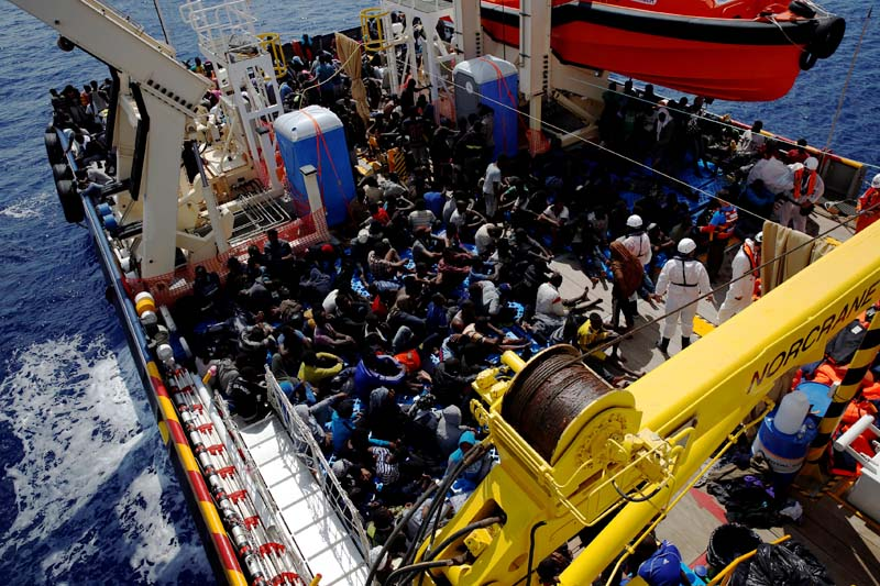 File- Migrants rest on the deck of the Migrant Offshore Aid Station (MOAS) ship Topaz Responder after being rescued around 20 nautical miles off the coast of Libya on June 23, 2016. Photo: Reuters