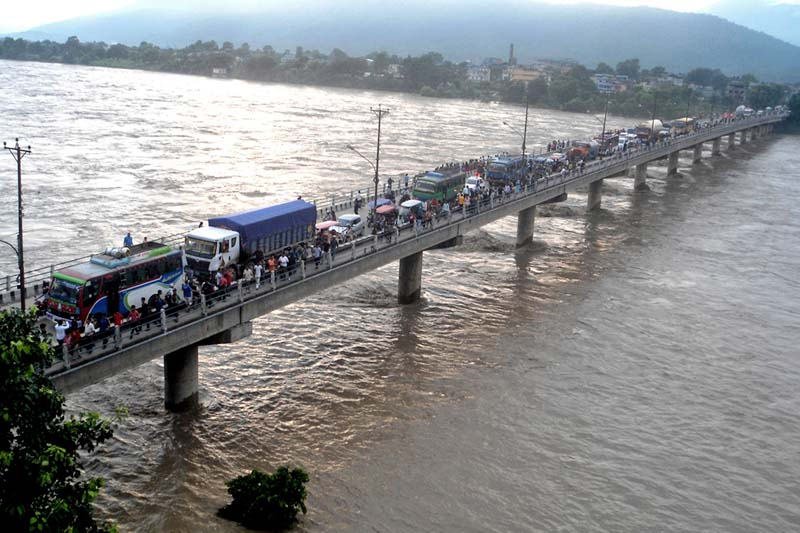 Scores of onlookers gather at the Narayani Bridge to look at the swollen Narayani River in Chitwan district, on Wednesday, July 27, 2016. Photo: RSS