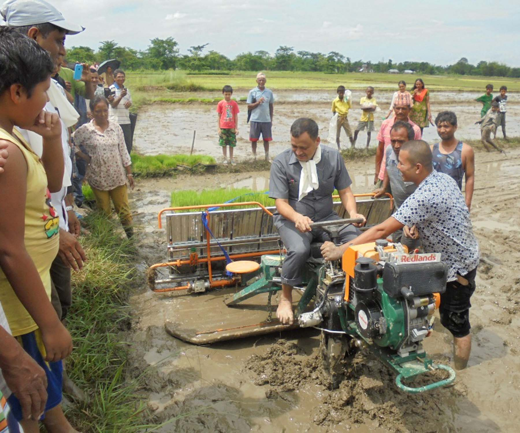 Jhapa Chief District Officer Madan Bhujel uses a machine for paddy plantation in a local farm in Puhantubari of Jhapa district, on Wednesday, July 13, 2016. Photo: RSS