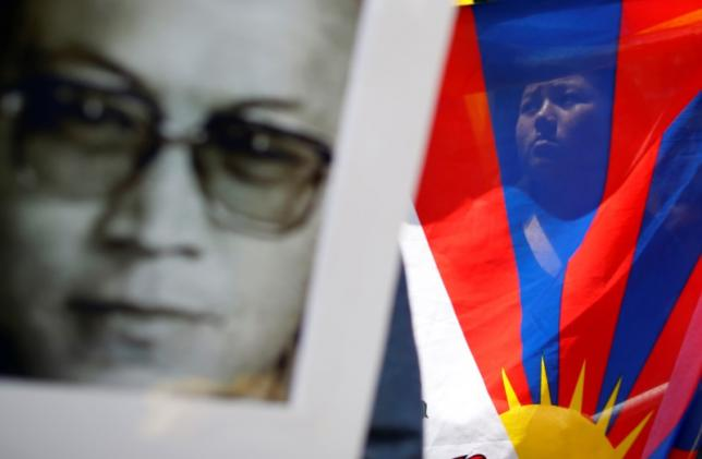 A protestor is seen through a Tibetan flag next to a photograph of Tenzin Delek Rinpoche during a demonstration outside the Chinese Consulate calling for justice over the imprisonment and death of Delek in Chicago, Illinois, United States, July 27, 2015.REUTERS/Jim Young/Files